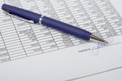 Blaue Feder auf dem gekennzeichneten Dokument. Lizenzfreies Stockfoto