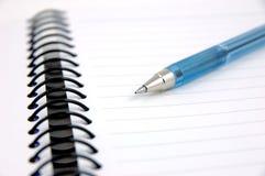 Blaue Feder auf Notizbuch Stockfotos