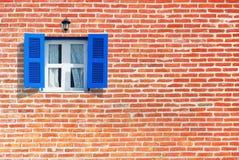Blaue Fenster auf Backsteinmauer Lizenzfreie Stockbilder