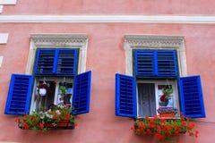 Blaue Fenster mit Pelargonien Stockfotografie