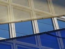 Blaue Fenster von einem Gebäude mit Markisen stockfotografie
