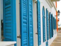 Blaue Fensterläden auf weißem Gebäude Stockfotografie