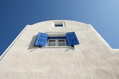 Blaue Fensterläden, blauer Himmel, weiße Wand Lizenzfreies Stockbild