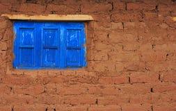 Blaue Fensterladenfenster der Adobe-Ziegelsteinwand Stockbild