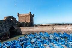 Blaue Fischerboote und defensiver Turm in Essaouira - Marokko stockfoto