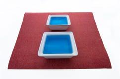 Blaue Flüssigkeit auf rotem Papier. Lizenzfreies Stockfoto