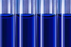 Blaue Flüssigkeit in den Rohren auf blured medizinischem Hintergrund Stockbilder