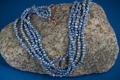 Blaue Frischwasserperlen auf Granit Stockbilder