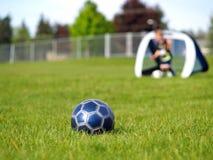 Blaue Fußball-Kugel und Spieler Stockfoto