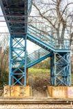 Blaue Fußgängerbrücke über Eisenbahn stockfoto