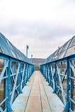 Blaue Fußgängerbrücke über Eisenbahn stockbilder