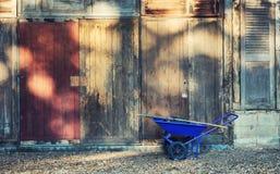 Blaue Gartenschubkarre gegen alte hölzerne Wand Stockbild