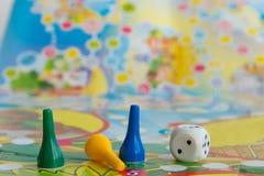 Blaue, gelbe und grüne Plastikchips, Würfel und Brettspiele für Kinder Lizenzfreie Stockfotos