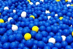 Blaue, gelbe und weiße Plastikbälle, Ball spielt Hintergrund Lizenzfreies Stockfoto