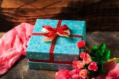 Blaue Geschenkbox mit Blumen und rotes Band mit rosafarbenen Blumen auf brauner Tabelle Lizenzfreie Stockbilder