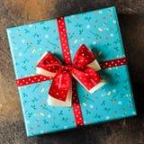 Blaue Geschenkbox mit Blumen und rotes Band mit rosafarbenen Blumen am braunen Tabellenfrauentag Stockbilder