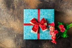 Blaue Geschenkbox mit Blumen und rotes Band mit rosafarbenen Blumen am braunen Tabellenfrauentag Stockfoto