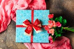 Blaue Geschenkbox mit Blumen und rotes Band mit rosafarbenen Blumen am braunen Tabellenfrauentag Stockfotografie
