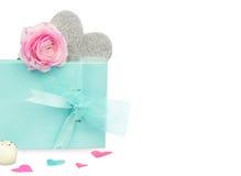 Blaue Geschenkbox mit Bogen, silbernes Herz, rosa Blume auf weißem Hintergrund Stockbild