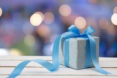 Blaue Geschenkbox mit Bokeh-Hintergrund lizenzfreie stockfotos