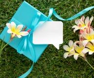 Blaue Geschenkbox mit einem Bogen, leere Anmerkung für Text und Blumen, Stockfotografie