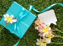 Blaue Geschenkbox mit einem Bogen, leere Anmerkung für Text und Blumen Stockfotografie