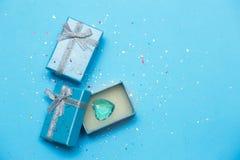 Blaue Geschenkbox mit Schmuck und Kristallherzen Hintergrund f?r eine Einladungskarte oder einen Gl?ckwunsch stockfotos