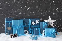 Blaue Geschenke mit Weihnachtsdekoration, schwarze Zement-Wand, Schnee, Schneeflocken Stockfoto