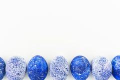 Blaue gesprenkelte Ostereier mit Kopienraum auf weißem Hintergrund Flache Lage Beschneidungspfad eingeschlossen Lizenzfreie Stockbilder