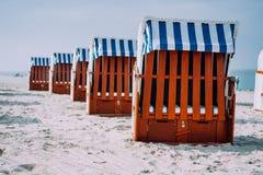 Blaue gestreifte überdachte Holzstühle steht in der Linie auf sandigem Strand am sonnigen Tag Travemunde, Luebeck, Deutschland stockfotografie