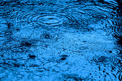 Blaue getonte Wasseroberfläche plätschert und spritzt im fallenden Regen stockfotos
