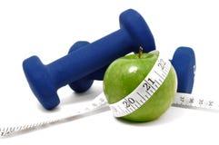 Blaue Gewichte, grüner Apple und Band-Maß Stockbild
