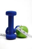 Blaue Gewichte, grüner Apple und Band-Maß Lizenzfreie Stockfotografie
