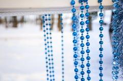 Blaue Girlanden und silberne Weihnachtsbälle und -lametta auf Schwingen Lizenzfreies Stockbild