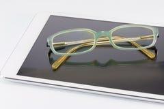 Blaue Gläser auf digitalem Tabletten-PC stockbilder