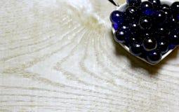 Blaue Glaskugeln auf hölzernem Hintergrund Lizenzfreie Stockbilder