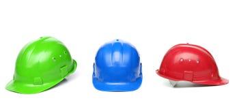 Blaue, grüne, rote Schutzhelme Stockfoto