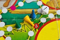 Blaue, grüne und gelbe Plastikchips und Würfel in den alten Brettspielen für Kinder Lizenzfreies Stockbild