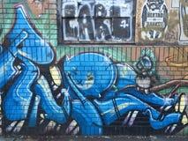 Blaue Graffiti-Backsteinmauer stockbild