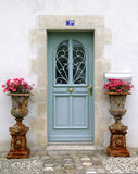 Blaue hölzerne Tür mit Blumenanlagen Lizenzfreie Stockfotografie