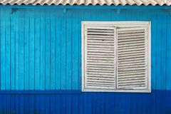 Blaue hölzerne Wand mit Fenster stockbild