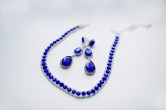 Blaue Halskette und Ohrringe auf weißem Hintergrund am Morgen lizenzfreie stockfotos