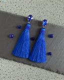 Blaue handgemachte Ohrringe mit Kristallen und Quasten Stockfoto