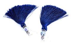 Blaue handgemachte Quastenohrringe auf einem weißen Hintergrund Stockbild