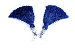 Blaue handgemachte Quastenohrringe auf einem weißen Hintergrund Stockbilder