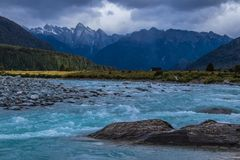 Blaue hetzende Wellen von Fernfluß unter Bergen stockfotos