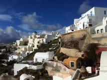Blaue Himmel über Oia und die rehabilitierten Häuser, welche die Steigung umarmen Lizenzfreies Stockbild