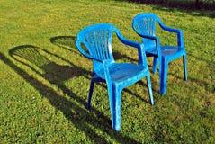 Blaue Hinterhofgartenstühle umgeben durch einen Garten Stockfoto
