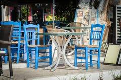 Blaue Holzstühle und Tabelle an der traditionellen griechischen Taverne Lizenzfreie Stockfotos