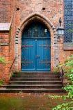 Blaue Holztür, Eingang zu einer alten Ziegelsteinkirche Stockfotografie